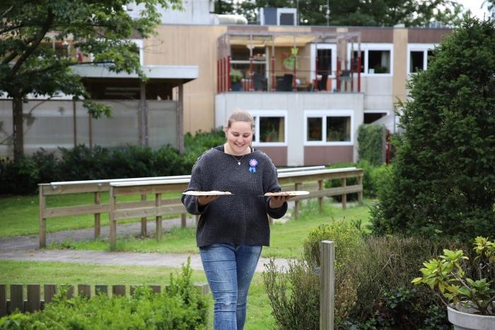Een net geslaagde leerling brengt pizza's naar de bewoners.