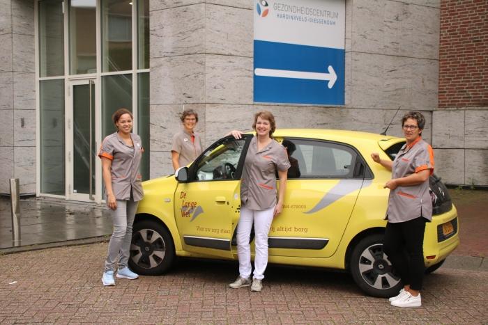 Het wijkteam voor de entree naar het souterrain van het Gezondheidscentrum, waar het nieuwe wijkkantoor is gehuisvest.