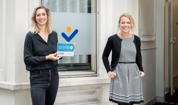 Aandachtsfunctionaris Annelies Brasjen (links) en Joëlle van Kommer bij Stadsring51 met het Keurmerk 'Meldcode huiselijk geweld'.