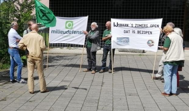 De actievoerders protesteren voor de deuren van de ijsbaan.
