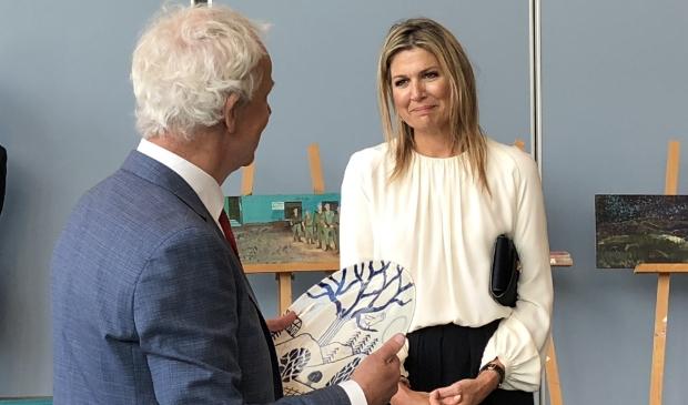 Gerrit Valk, voorzitter van de Raad van Bestuur van Veteraneninstituut, overhandigt koningin Máxima een kunstwerk.