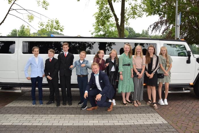 De groep 8 sterren poseren met hun leerkracht voor de stoere limousine