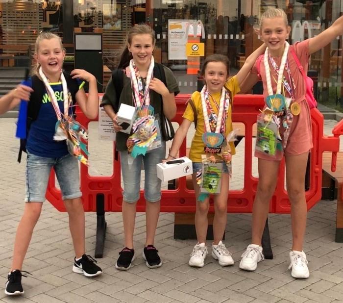 Tirsa, Sarah, Britt en Fenna staan trots op de foto met hun medailles.