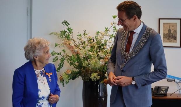 Burgemeester Poppens reikt een lintje uit aan Moppie Holla-Fontijn.
