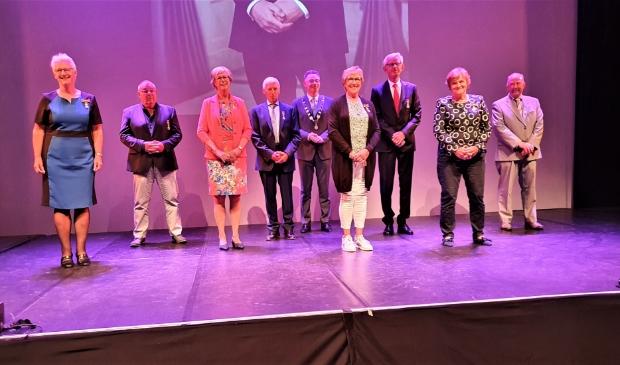 Burgemeester Isabelle met de acht gedecoreerden in Theater aan de Slinger