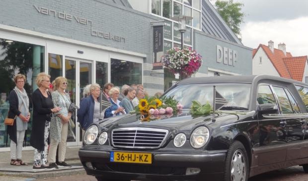 De rouwauto stopt even bij Boekhandel Van de Ven.