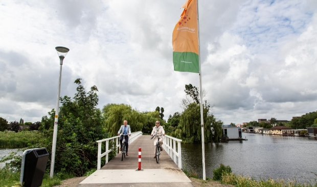 Wethouder Mariëtte Sedee en Marco Kastelein van het hoogheemraadschap nemen de vernieuwde brug in gebruik.
