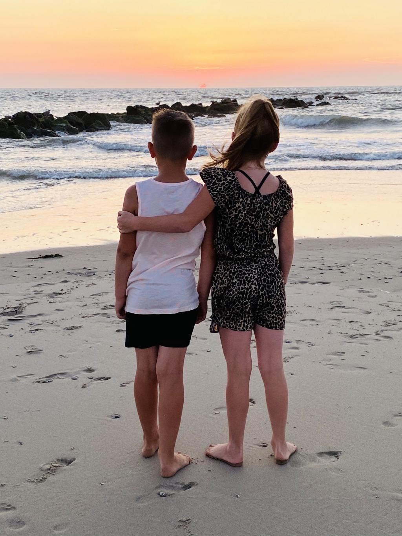 Echte broer en zus liefde op deze foto. Typisch een koppeltje 'niet met elkaar en niet zonder elkaar kunnen'. Ze kijken samen op Texel naar het laatste stukje van de zonsondergang. Rilana Westbroek © BDU Media