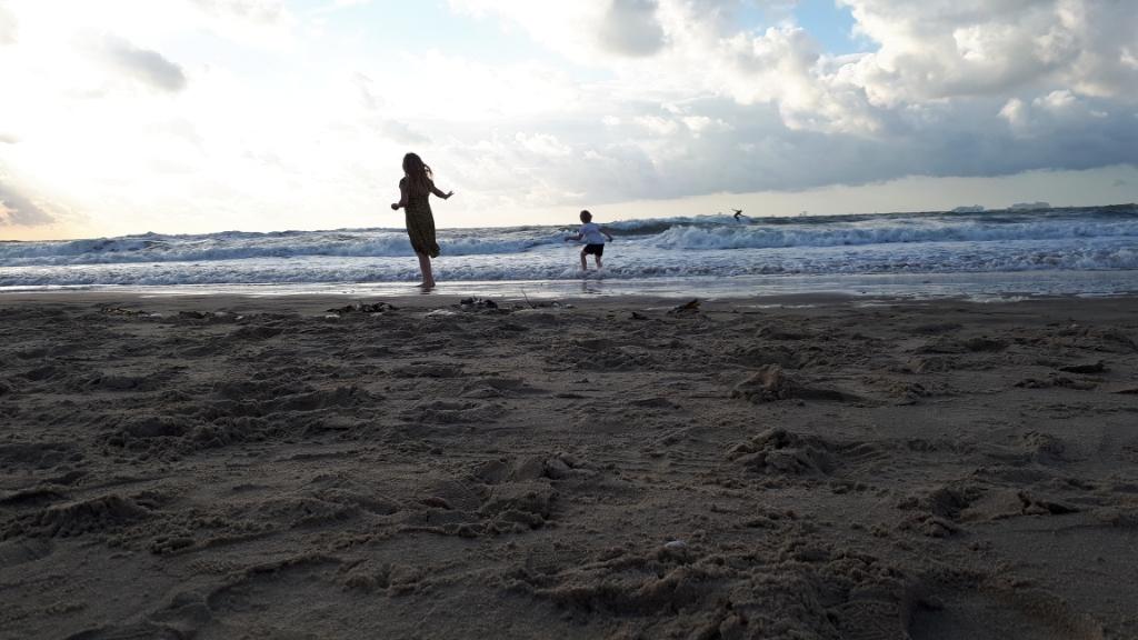 Timo en Sofie aan de Scheveningse kust op zondag 23 augustus. Timo imiteert de surfer op de achtergrond, terwijl zijn zus Sofie staat te genieten van de wind en ondertussen een oogje in het zeil houdt. Liesanna van de Bospoort © BDU Media