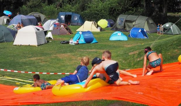 Heuvelaf glijden met op de achtergrond het tentenkamp.