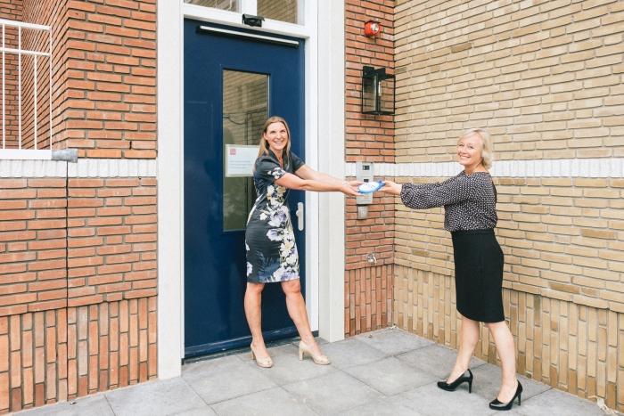 De symbolische sleuteloverdracht tussen Marieke Heilbron, directeur-bestuurder van Elan Wonen, en Tamara Pieterse, bestuurder van Zorgbalans.