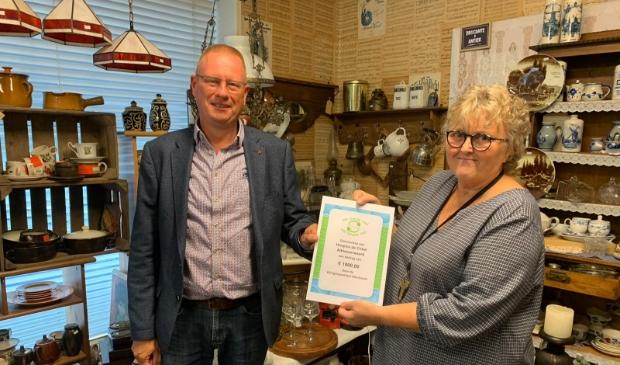 Uit handen van Bartha Visser (Kringloopwinkel Sliedrecht) ontvangt Nico van der Veen (Stichting vrienden van hospice De Cirkel) een cheque van 1000 euro.