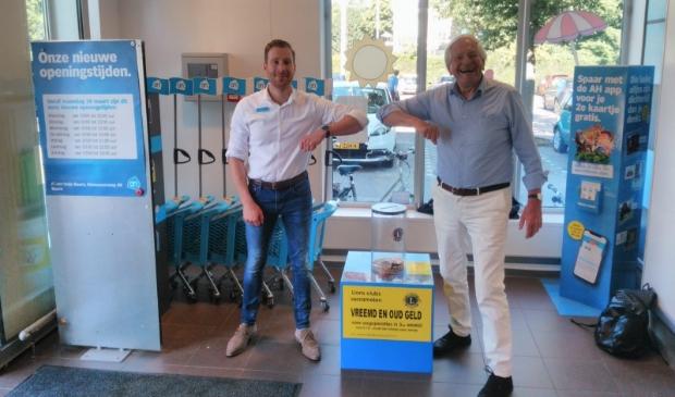 Albert Heijn manager Albert Buijs samen met Herman Olde Heuvelt van Lionsclub Eemland bij de Lions geld verzamelzuil.