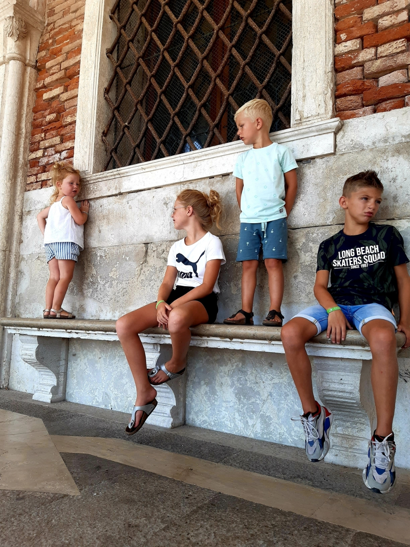 """,,Prachtig Venetië augustus 2020. Onze 4 schatten (Anne, Bas, Seth en Noor) komen bij van alle indrukken en de warmte op een bankje in de schaduw."""" Eén gezin, maar stuk voor stuk uniek Marianne van Trigt © BDU Media"""