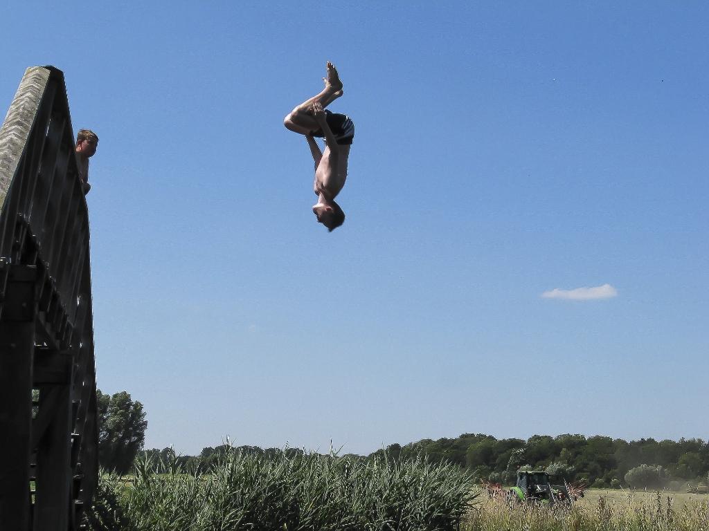 Terwijl de boer zijn land bewerkt springt de jeugd van een brug het verkoelende water in. Het doet mij terugdenken aan de lange zomervakanties toen ik nog jong was, een halve eeuw geleden.  Begin juli 2020, Zuidlaren (Drenthe).  GerritJan Fransen © BDU media