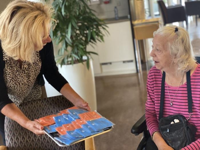 Zorgdirecteur Helma Meeuwissen van A.G. Bodaan biedt een mondkapje aan aan een cliënt van Kennemerhart