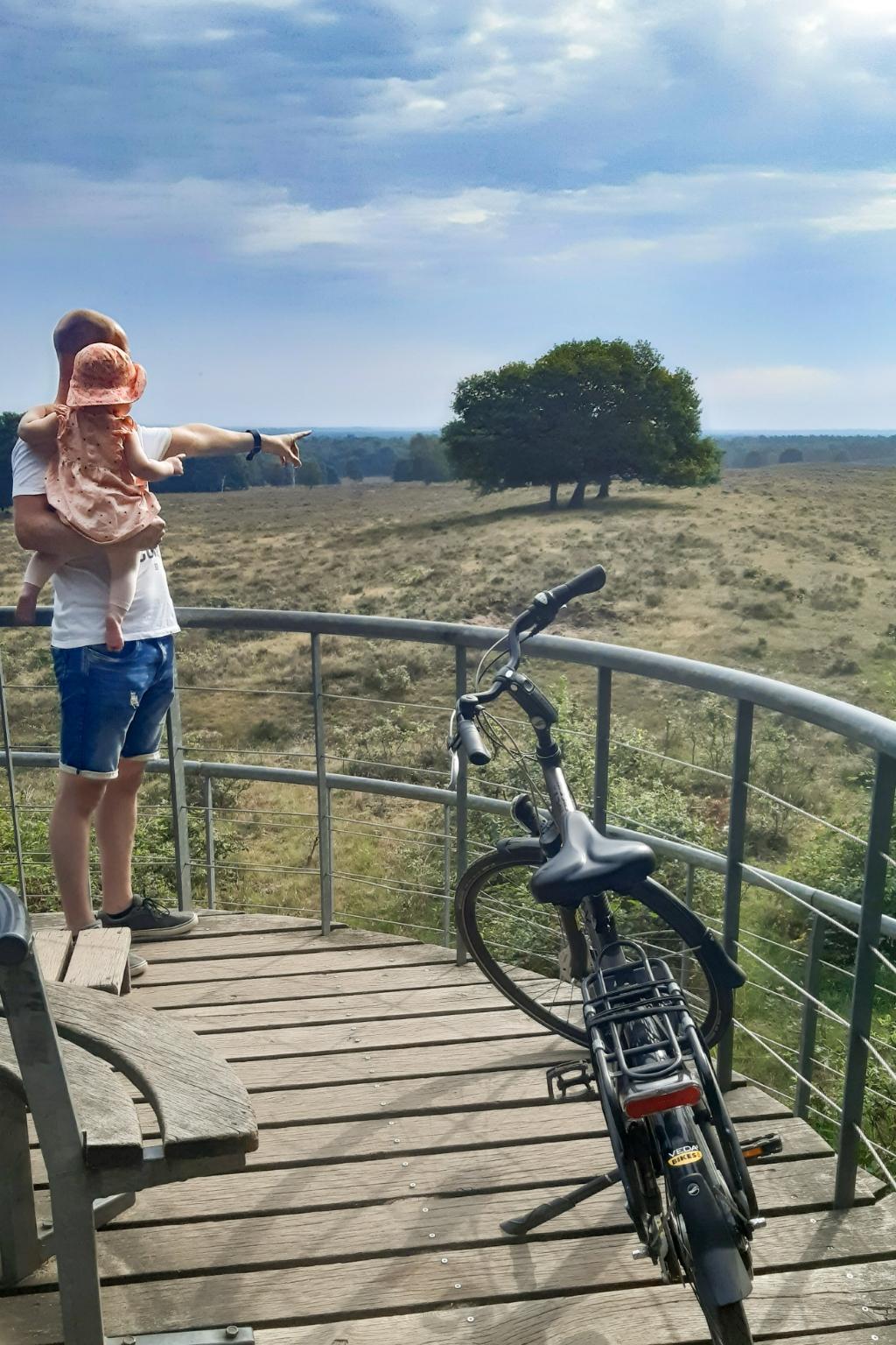Remco en Mila van der Eijk staan op de foto kijkend naar het natuurgebied Planken Wambuis vanuit het uitkijkpunt Valenberg. Kim van der Eijk © BDU Media