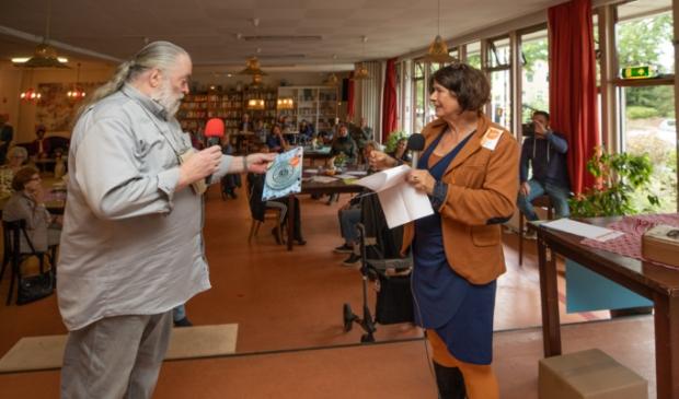 <p>Marjo Stam reikt het eerste Lokaal-O kookboek uit aan Koos Rooyen, gast van het eerste uur van Lokaal-O. &nbsp;</p>