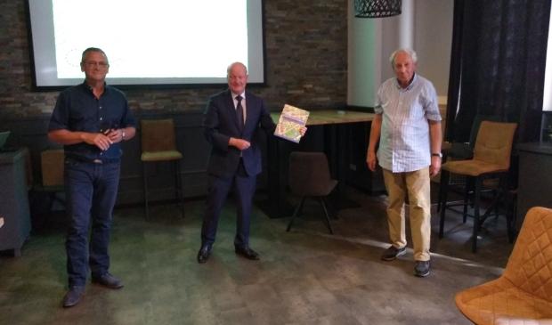 Johan van Impelen (links) en Jan Kleinpenning (rechts) overhandigen het eerste boek aan burgemeester Ruud van Bennekom.