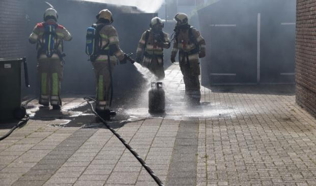 Brandweermannen koelen de gasfles die in de brandende schuur stond.