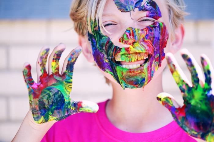 Een kind met verf op gezicht en handen