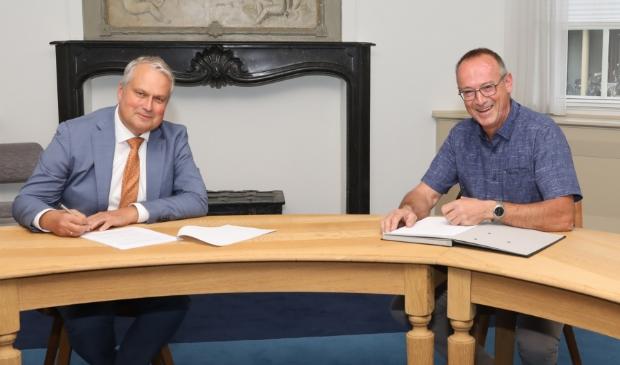<p>Wethouder Wim Oosterwijk en Henny Smink (directeur Smink Vastgoed) tekenen van de overeenkomst bouwplan de Hofstee in Doornsteeg in Nijkerk.</p>