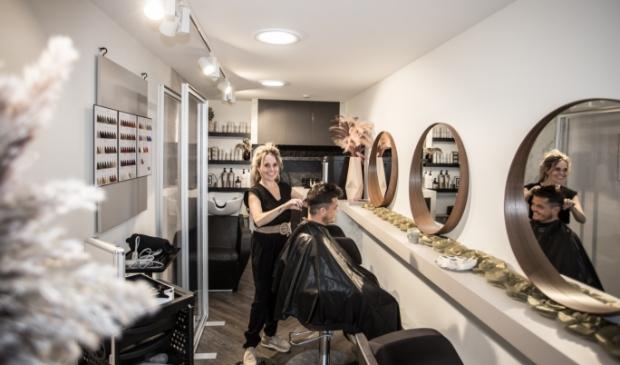 Marianne Minne - van Delen knipt Gerben Davelaar, haar eerste klant in de nieuwe salon.