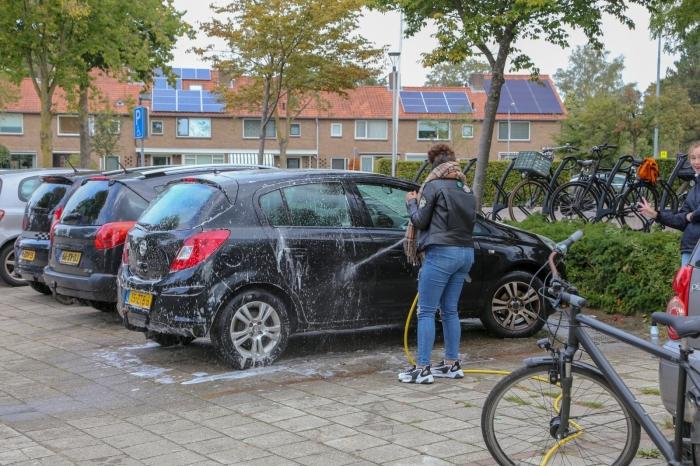 Tieners druk in de weer met auto's wassen.