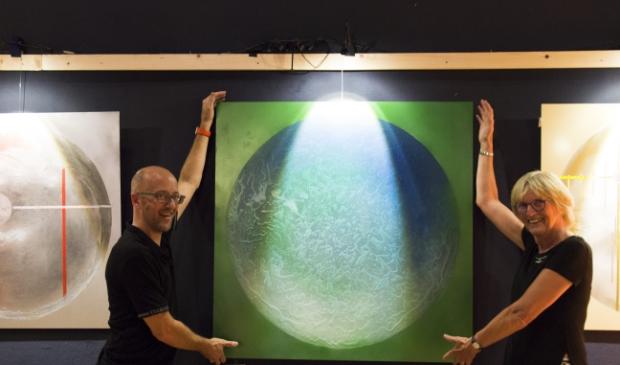 <p>Peter Kluskens en Wil de Reus tonen een van de schilderijen.</p>