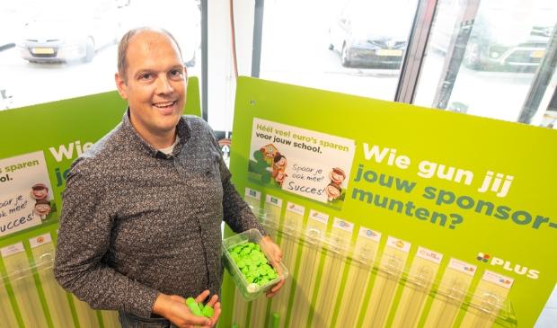 <p>Elbert van den Doel bij de wand met 'spaarbuizen' in zijn supermarkt.</p>