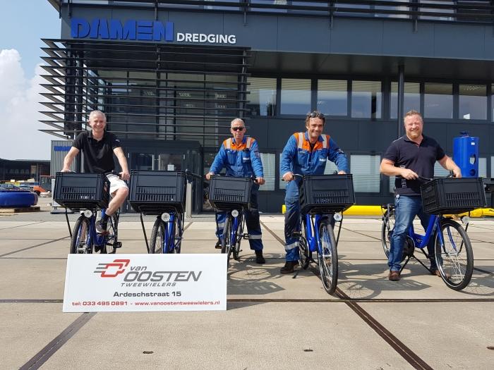 De bedrijfsfietsen worden overhandigd aan een enthousiast Damen Dredging team