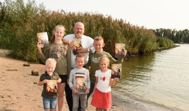 <p>Jan van Wingerden met zijn kleinkinderen, die allemaal het boek vasthouden, bij de Merwede.&nbsp;</p>
