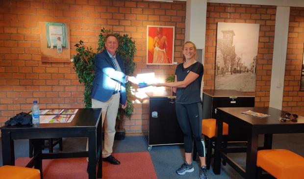 <p>Speerwerpster No&euml;lle Roorda overhandigt de eerste Wegwijzer aan wethouder Rob Ellermeijer.</p>