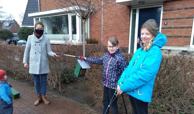 Auke Otto overhandigt de vogelhuisjes aan Merel en Hanna.