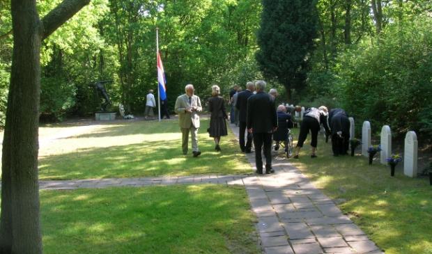 Opname tijdens de bloemenhulde bij de graven van omgekomen Velsenaren op begraafplaats Duinhof, georganiseerd door het gemeentebestuur