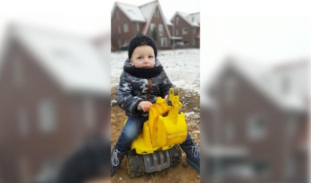 Jesse de Rooij (2 jaar) op graafmachine voor het huis in Kernhem