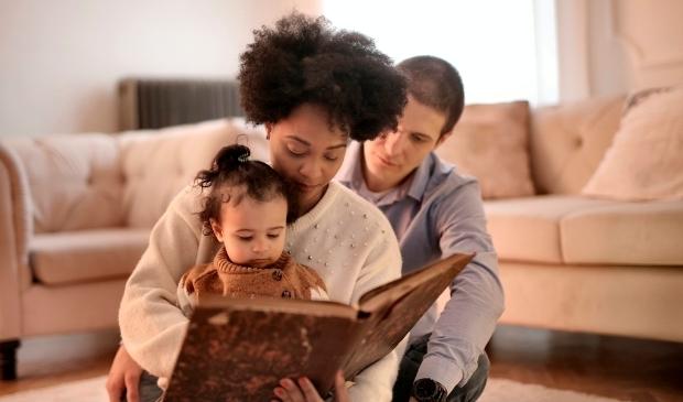 Vader en moeder lezen voor aan dreumes.