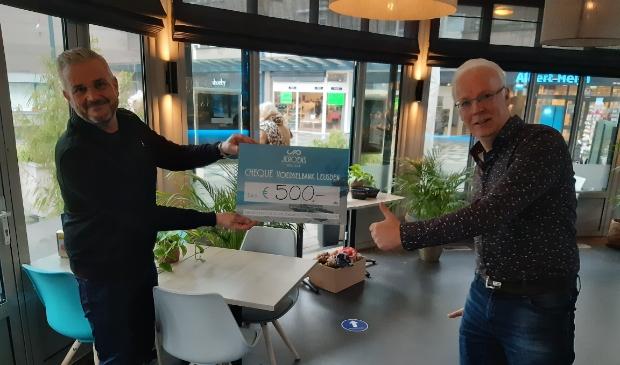 <p>Jeroen Dammers (links) van Jeroens Paviljoen overhandigt de cheque van 500,= euro aan penningmeester Henk Krakers van de Voedselbank.</p>