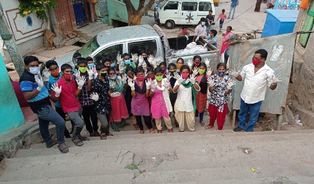 <p>De kinderen hielpen mee om de kerstpakketten, die zij<br>hadden ingepakt, aan de mensen in de sloppenwijk te geven.</p>