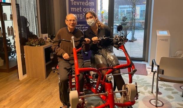 <p>Kelley probeert samen met bewoner meneer Schippers de nieuwe fiets uit.</p>