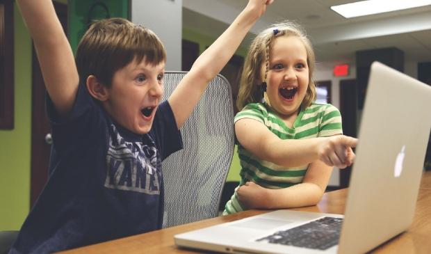 Juichende kinderen achter een laptop