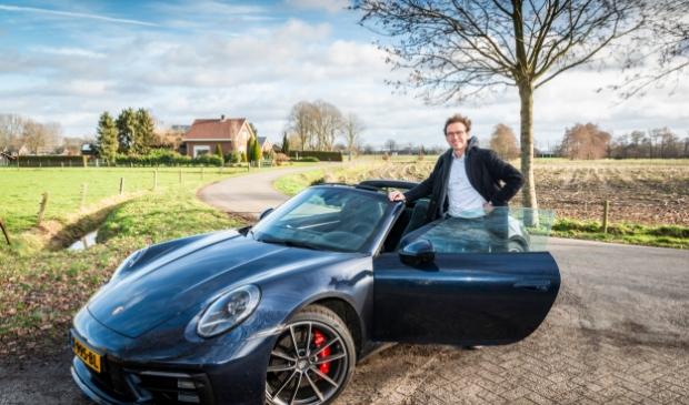 <p>Carl Koetsier op de foto met de exclusieve auto van een klant.</p>