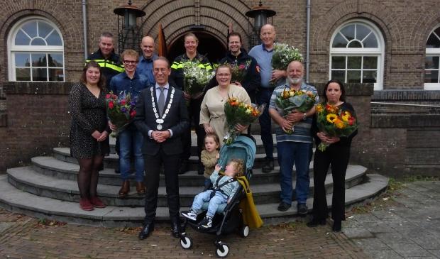 <p>Roos Knoote (naast de burgemeester) met haar kinderen en de redders en hupverleners.</p>