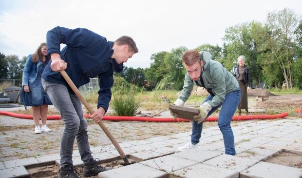 Op de foto zie je Jan-Dirk (18) uit groep A7 samen met Wim uit groep A6 stenen sjouwen voor op de pallet.