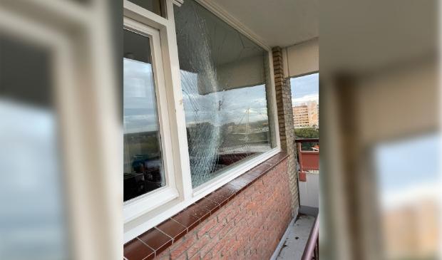 De schade aan het raam van de woning op elf hoog, veroorzaakt door een bouwkraan.