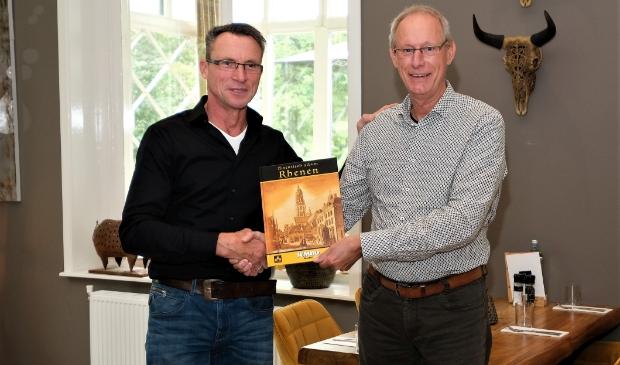 <p>Cornelis Mostert ontvangt uit handen van Dries Huisman het eerste nog te plakken exemplaar het Historisch album Rhenen.</p>
