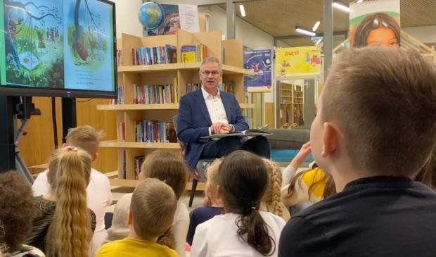 Wethouder Marco Verloop leest de kinderen van Achtbaan voor op het leerplein.