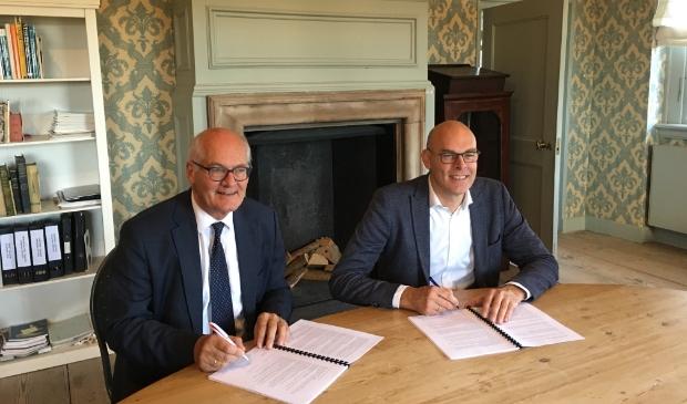 Wethouder Gerrit Boonzaaijer van de gemeente Utrechtse Heuvelrug en Herman Sietsma ondertekenen de overeenkomst in het Kasteel van Amerongen.