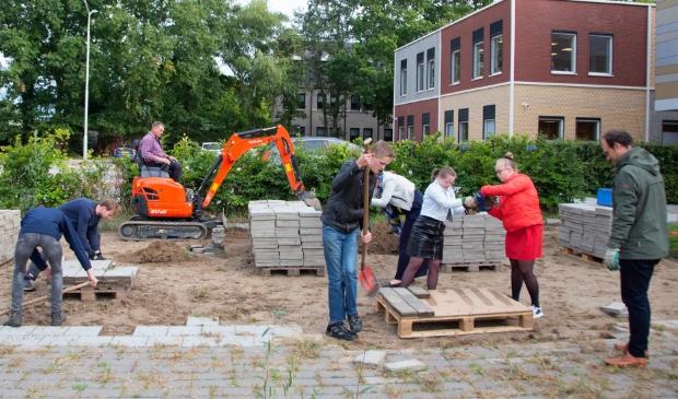 Kinderen, vrijwilligers en personeel werken samen aan de voorbereidingen voor de Schou-tenhoeve. Ton is actief op de kraan.