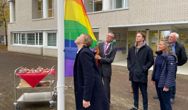 <p>Maarten, de zoon van Gerrit van der Meer, hijst de regenboogvlag. Burgemeester Gorter assisteert. De gebakjes (optimistjes!) staan al klaar</p>